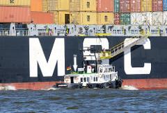 Die Gangway ist an Backbord des Containerschiffs MSC ROSELLA heruntergelassen. Das schnelle Lotsenschiff des Hafenlotsen ist längsseits gegangen und der Lotse ist bereit an Bord des Frachters zu gehen.