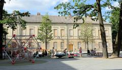 Moderner Kinderspielplatz beim Unabhängigkeitsplatz in Kaunas - im Hintergrund ein leerstehendes Gebäude - die Fenster sind mit Holzplatten vernagelt.