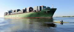 Der 336m lange und 45m breite Containerfrachter XIN SHANGHAI wurde 2006 gebaut und kann 9572 TEU Standardcontainer transportieren. Das Schiff fährt auf der Elbe Richtung Nordsee - im Vordergrund ein Kanu, das mit der Tide Richtung Hamburg gepaddelt w