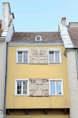 Fassadenreliefs in der Altstadt von Olsztyn.