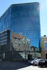 Spiegelung von historischer Architektur in der Glasfassade eines Bürogebäudes in der Tallinner Innenstadt.