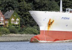 Schiffsbug des Frachtschiffs FIONA - am Elbufer Wohnhäuser mit Efeufassade.