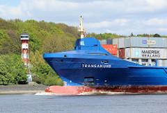 Das Frachtschiff TRANSANUND auf der Elbe vor Hamburg Wittenberge - im Hintergrund das Leuchtfeuer am Ufer der Elbe. Die 2007 gebaute TRANSANUND hat eine Länge von knapp 142m und kann 801 TEU Container transportieren.
