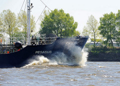Der 62m lange und 10m breite Tanker Pegasus fährt auf der Elbe vor dem Hamburger Bubendey Ufer; hoch spritz die Gischt am Bug des Tankschiffs