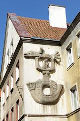 Steinrelief an einer Hauswand in der Innenstadt von Olsztyn - Nixe mit Fisch.