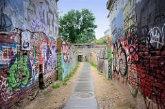 Schmale Gasse, Jono Meko skersvėjis im Stadtteil Užupis in Vilnius; Ziegelmauern ohne Putz - bunte Graffitis.