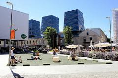Platz im Quartier Rotermanni in der Tallinner Innenstadt, Roseni  / Architektur Alt + Neu. Im Hintergrund das historische Gebäude einer Tischlerwerkstatt mit aufgesetzten futuristischen Türmen - Gestaltung Architekten Büro KoKo.