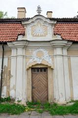 Pfarreigebäude mit religiösen Stuckmotiven bei der Kirche Himmelfahrt in Vilnius.