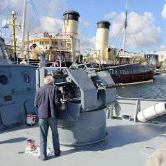 Schifffahrtsmuseum in Tallinn - ein Mechaniker arbeitet an einer Bordkanone eines Museumsschiff.