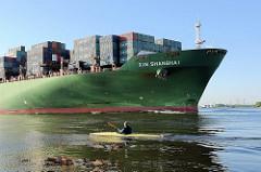 Bug des Frachters XIN SHANGHAI auf der Elbe bei Hamburg - ein Paddelboot fährt stromaufwärts.