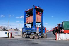 Ein Portalhubwagen / van carrier transportiert einen Container im Hamburger Hafen.