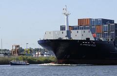 Der Frachter X PRESS FUJI läuft in den Hamburger Hafen ein - eine kleine Barkasse der Hamburger Hafenrundfährt fährt vor dem Bug des Schiffs.