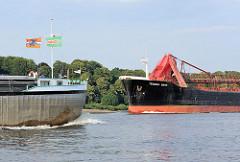 Zwei Frachtschiffe begegnen sich auf der Unterelbe - ein Binnenschiff fährt Richtung Hamburg, während ein Seeschiff elbabwärts fährt.