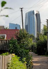 Neu + Alt - ursprüngliche Wohnhäuser, schmaler Sandweg - moderne Hochhaustürme - Stadtteil Šnipiškės in Vilnius.