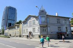 Traditionelle Holzarchitektur - einstöckige Holzgebäude mit Erkerturm / Eckgebäude in der Straße Liivalaia in Tallinn - im Hintergrund die moderne Architektur vom Radisson Blu Hotel Olümpia / alt + neu.