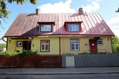 Doppelhaus mit unterschiedlich farbig gestalteter Fassade und Zaun - Straße Preesi in Tallinn.