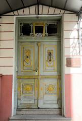 Alte Holztür, Eingangstür; Türblatt mit farblich abgesetzten Schnitzereien und Perlleisten - Bilder aus Tallinn, Estland.