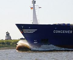 Die 1994 auf der Hambuger Sietas Werft gebaute CONCEIVER hat eine Länge von 117m und eine Ladekapazität von 547 Containern TEU. Im Hintergrund das alte Leuchtfeuer hinter dem Deich von Lühe.