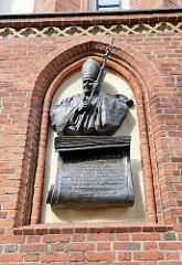 Bronze-Plakette von Papst Johannes Paul II. an der Fassade der St. Jakob Kathedrale in Olsztyn.