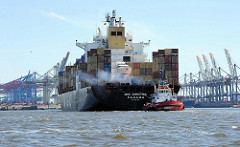 Der Containerfrachter MSC CHRISTINA wendet mit Schleppperhilfe auf der Elbe - im Hintergrund die Conatinerbrücken des Waltershofer Hafens.
