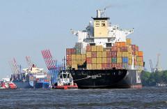 Schlepper am Heck des mit Containern hochbeladenen Containerschiffs MSC ROSELLA. Ein Container Feeder kommt dem Frachschiff in der Fahrtrinne entgegen - eine Hafenfähre kreuzt die Elbe.