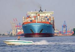 Die COLUMBINE MAERSK läuft aus dem Hamburger Hafen aus - im Hintergrund die Containerbrücken des HHLA Terminals Burchardkai. Der 2002 gebaute Frachter hat eine Länge von 347m und kann 8890 Standardcontainer transportieren. Ein Sportboot kreuzt in sch