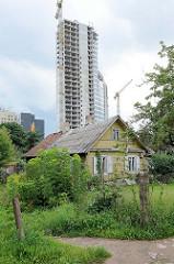Neu + Alt - ursprüngliches Wohnhaus, traditionelle Holzbauweise / Holzhaus - Baustelle eines Hochhauses / Rohbau; Stadtteil Šnipiškės in Vilnius.