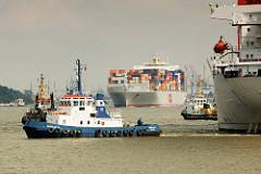Bilder aus dem Hamburger Hafen - Schlepper ziehen einen Frachter vom Kai - Containerschiff mit Containern beladen läuft aus.