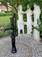 Alte öffentliche Wasserentnahmestelle, Wasserpumpe in Olsztyn - Steinskulpturen.