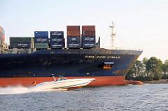 Die im Jahr 2005 gebaute CMA CGM Otello hat eine Länge von 335m und eine Breite von fast 43 m. Das Schiff kann 8488 Standardcontainer transportieren. Ein schnelles Sportboot überholt das Frachtschiff auf der Elbe.