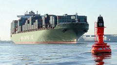 Das Frachtschiff XIN SHANGHAI verlässt den Hamburger Hafen - die Containerladung ist hoch an Deck des Schiffs gestapelt. Das 336m lange und 45m breite Schiff wurde 2006 gebaut und kann 9572 TEU Standardcontainer transportieren.Im Vordergrund eine rot