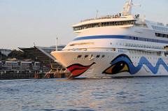 Schiffsbug des 21 Kn schnellen Passierschiffs AIDA AURA - im Hintergrund die moderne Büroarchitektur des Docklands.
