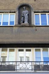 Skulptur Mauerer mit Schürze / Kittel, Kelle an einer Ziegelsäule; Hausfassade in Tallinn, Baujahr 1936.