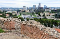 Blick über die Reste der Burgmauern auf dem Burgberg zum Fluss Neris und den Hochhäusern im Stadtteil Šnipiškės in Vilnius.