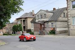 Wohnhäuser, teilweise mit Holzfassade - Straße  A. Mackevičiaus in Kaunas - rotes Sportauto in Fahrt.
