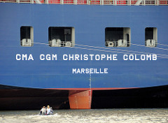 Heck des Containerschiffs Christophe Colomb im Hamburger Hafen / Terminal Burchardkai. Ein kleines Sportboot fährt dicht anden Riesenfrachter heran.