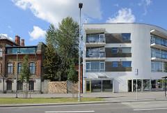Alt + Neu, historische und moderne Architektur in Tallinn - halbrundes Wohnhaus mit Geschäften / Backsteingebäude, Gewerbegebäude mit vergitterten Fenstern.
