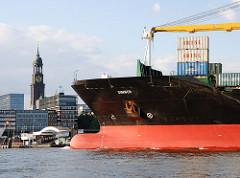 Der Containerfrachter SIMBER läuft aus dem Hamburger Hafen aus - das Frachtschiff passiert gerade die Überseebrücke - im Hintergrund der Turm der St. Micheliskirche, dam Wahrzeichen Hamburgs.