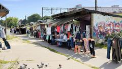 Provisorische Verkaufsstände - Kleidungsläden an den Bahngleisen in Olsztyn.