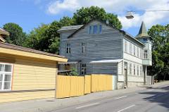 Alte Holzhäuser - traditionelle Holzarchitektur in der Straße Luise in Tallinn; gelbe Hausfarbe, Holzzaun - einstöckiges Wohnhaus mit Erkerturm, spitzes Dach.