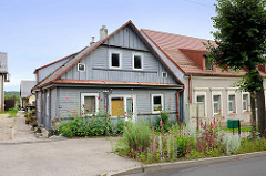 Holzhaus mit blühenden Stockrosen an der Straße - Bilder aus Kaunas / Litauen.