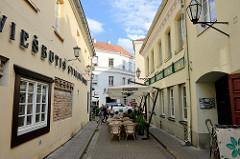 Strasse im ehem. jüdischen Viertel in Vilnius; schmale Gasse  - Tische von Restaurants / Cafés auf der Straße.