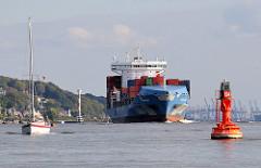 Das Feeder Schiff CAFER DEDE hat den Hamburger Hafen verlassen und fährt auf der Elbe Höhe Hamburg Blankenese - im Hintergrund ist das Leuchtfeuer zu erkennen. Ein Segelboot fährt mit seinem Hilfsmotor knapp ausserhalb der Fahrrinne für die Seesc