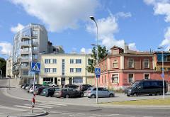 Moderne und historische Architektur in Tallinn, alt + neu - Wohnblock mit Glasfassade, leerstehendes Holzhaus mit vernagelten Fenstern.