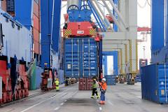 Verladung eines Containers am Containerterminal Burchardkai im Hamburger Hafen - die Stahlbox wird vom Containerschiff am Kai abgesetzt.