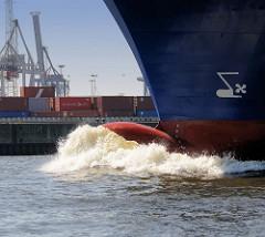 Wulstbug mit Bugwelle / Gischt eines Frachters auf der Elbe im Hamburger Hafen - im Hintergrund ein Containerlager.