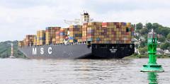 Der Frachter MSC INES mit Containern hoch beladen auf der Höhe von Hamburg Blankenese. Im Vordergrund eine grüne Fahrwassertonne auf der Elbe. Das Container-Transportschiff kann 9113 Contianer TEU laden und fährt bei einem Tiefgang von 14,50m 25,6 kn