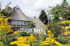 Bauerngarten in Hamburg Curslack - blühende Blumen, Wäsche hängt zum Trocknen  in der Sonne; Fachwerkhaus mit Reetdach.