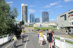 Fussgängerbrücke Baltasis tiltas / Weiße Brücke über die Neris; Panorama der modernen Hochhäuser im Stadtteil Šnipiškės in Vilnius.