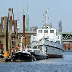 An einem Ponton im Reiherstieg der Verbindung im Hamburger Hafen zwischen Norderelbe und Süderelbe liegen an einem Pontont und Holdalben Barkassen und das ehemalige Fährschiff Fahrgastschiff INSEL HIDDENSEE. Im Hintergrund sind der Turm der Michaelis